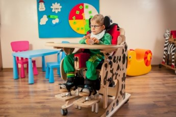 a child placed in the DALMATIAN Chair & Stander